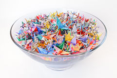 Paper cranes. Thousand cranes in a big glass bowl on a white background royalty free stock image