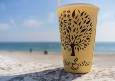 Paper cup on the beach. Paper cup with a drink on the beach Royalty Free Stock Photo