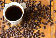 A paper cup of black coffee and coffee beans on table Royalty Free Stock Photography