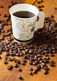 A paper cup of black coffee and coffee beans on table Royalty Free Stock Photos
