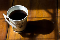 A paper cup of black coffee on table Stock Photos