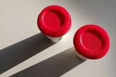 2 paper Cup boxes with a red lid are on the table in the cafe. Coffee to go. Morning stock photography