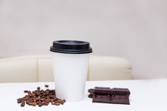 Paper cup with chocolate chips and coffee beens Royalty Free Stock Photography