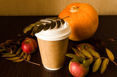 Paper cup with coffee on autumn background. Coffee cup and pumpkin, still life with foliage on black wood Royalty Free Stock Photography
