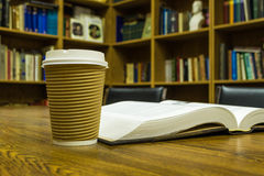 Paper cup of coffee and book on wooden table. In library. time for break Royalty Free Stock Photography