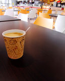 Paper cup of coffee on cafeteria table top