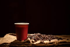 Paper cup of coffee and coffee beans on black background royalty free stock image