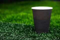 Paper cup with coffee cost on green grass.  royalty free stock photography