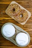 Paper cup for coffee, disposable ecological coffee supplies. Donuts on paper trays. Wooden table. Top view royalty free stock images