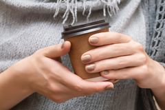 Paper cup with coffee in female hands.  stock image