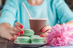 Paper cup of coffee and macaroons on table Stock Photo