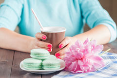 Paper cup of coffee and macaroons on table Stock Images