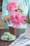 Paper cup of coffee and macaroons on table Stock Image