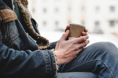 Paper cup of coffee in man`s hands. Hipster man holds cup of coffee in his hands royalty free stock image