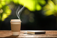 Paper cup of coffee. With smoke and book in the garden Royalty Free Stock Photo