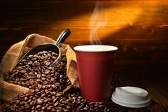 Paper cup of coffee with smoke and coffee beans Royalty Free Stock Photos