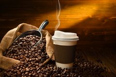 Paper cup of coffee with smoke and coffee beans on old wooden Stock Images