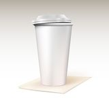 Paper cup for coffee standing on a napkin. Stock Photos