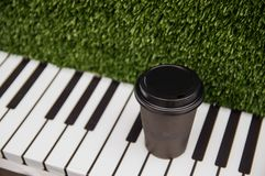 A paper cup of coffee stands on the keys of a piano on a green grassy background stock photo