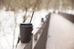 Paper cup with coffee stands on a metal handrail on the bridge stock image