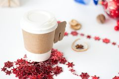 A paper cup of coffee, peppermint mocha, displayed with christmas decorations on white background. Paper cup of coffee surrounded by Christmas decorations on Royalty Free Stock Photos