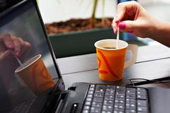Paper cup of coffee on the table near the laptop Stock Images