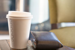 Paper Cup Coffee. A white paper cup of coffee with money bag on the brown table under bokeh background Stock Photos