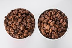 Paper cup filled with coffee beans. On a white background. to go or take away drink. top view Stock Photo