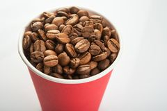 Paper cup filled with coffee beans. On a white background. to go or take away drink Royalty Free Stock Photography