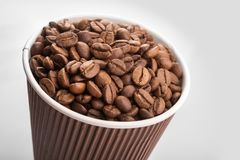 Paper cup filled with coffee beans. On a white background. to go or take away drink Royalty Free Stock Photo