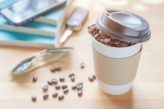 A paper cup of full roasted aroma coffee beans with blurred back. Ground of books, smartphone, sunglass and key, good morning concept Stock Images