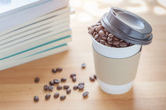 A paper cup of full roasted aroma coffee beans with blurred back. Ground of books and some fallen coffee beans on wooden board , business concept Royalty Free Stock Image