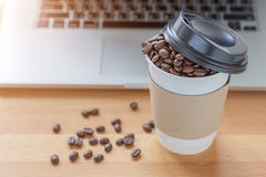 A paper cup of full roasted aroma coffee beans with blurred back. Ground of some fallen coffee beans on wooden board and laptop, business concept Royalty Free Stock Photos