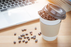 A paper cup of full roasted aroma coffee beans with blurred back. Ground of some fallen coffee beans on wooden board and laptop, business concept Stock Photos