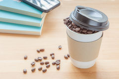 A paper cup of full roasted aroma coffee beans with blurred back. A paper cup of full roasted aroma coffee beans and some fallen on wooden board with blurred Royalty Free Stock Photos