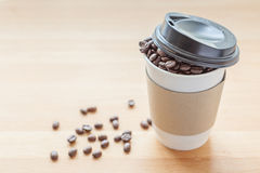 A paper cup of full roasted aroma coffee beans, good morning con. A paper cup of full roasted aroma coffee beans, selective focus on paper cup and blurred Royalty Free Stock Photo