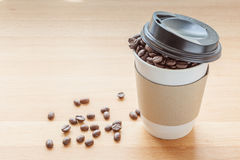 A paper cup of full roasted aroma coffee beans, good morning con. A paper cup of full roasted aroma coffee beans and some fallen on wooden board background Stock Photography