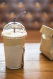 Paper cup of iced coffee on wooden table stock image