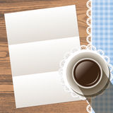 Paper with cup with lace doily and ribbon border on wood Royalty Free Stock Image
