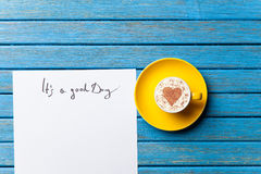 Paper and cup lying on the table Royalty Free Stock Images