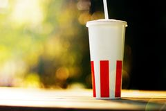 Paper cup with a straw and standing on wooden park bench, green bokeh background, sunshine stock images