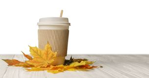 Paper cup take away mug and autumn leaves on white wood. Paper cup of coffee or tee to go take away mug fast food and autumn leaves on white wood stock photo