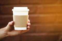 Paper cup of takeaway coffee in the hand. Place for your text or logo Stock Photo