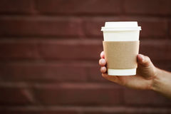Paper cup of takeaway coffee in the hand. Place for your text or logo Royalty Free Stock Images