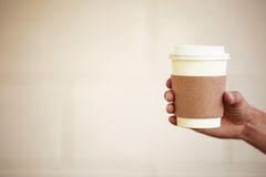 Paper cup of takeaway coffee in the hand. Place for your text or logo Royalty Free Stock Photos