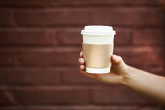 Paper cup of takeaway coffee in the hand. Place for your text or logo Royalty Free Stock Photography