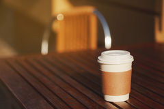Paper cup of takeaway coffee. On the wooden table in cafe. Place for your text or logo Stock Image