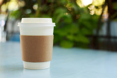 Paper cup of takeaway coffee. On the wooden table in cafe. Place for your text or logo Royalty Free Stock Images