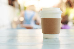 Paper cup of takeaway coffee. On the wooden table in cafe. Place for your text or logo Stock Photo