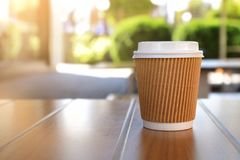 Paper cup with tasty hot coffee on wooden table. Outdoors Royalty Free Stock Photo